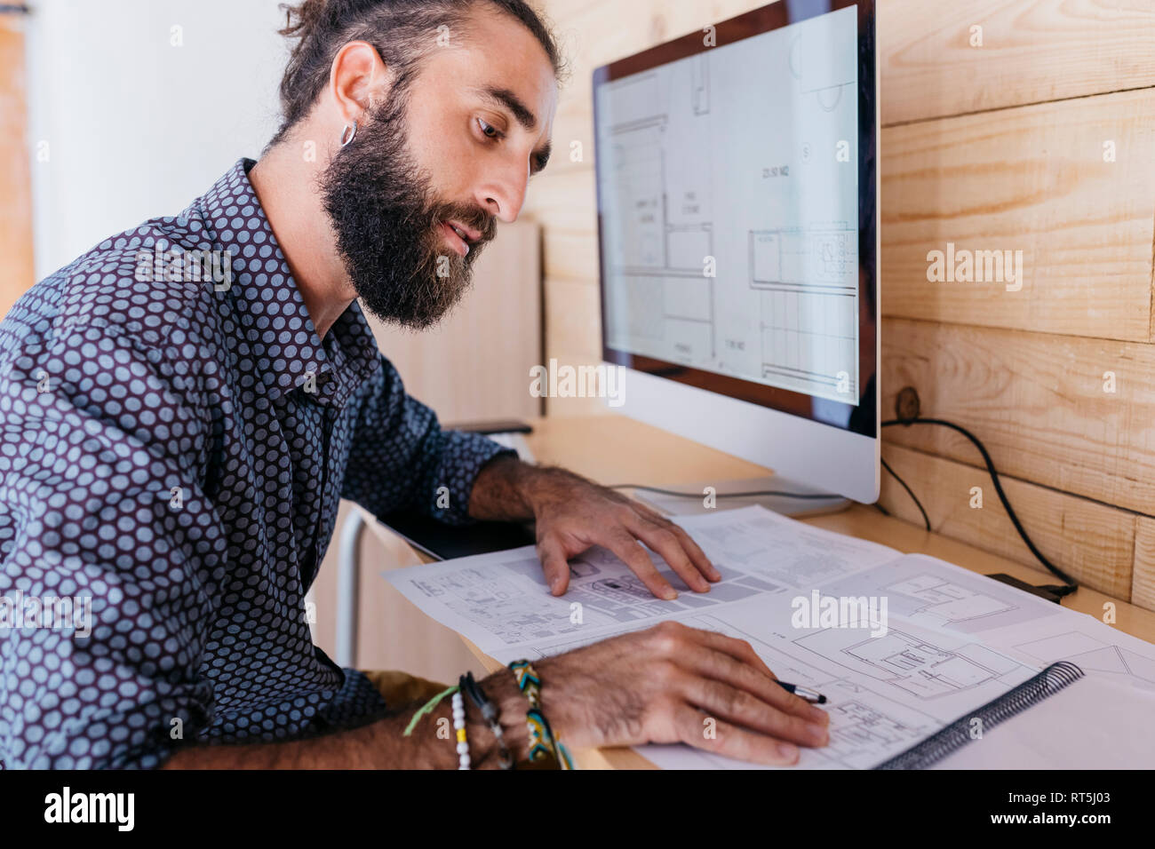 Young architect working at home with blueprints and computer - Stock Image