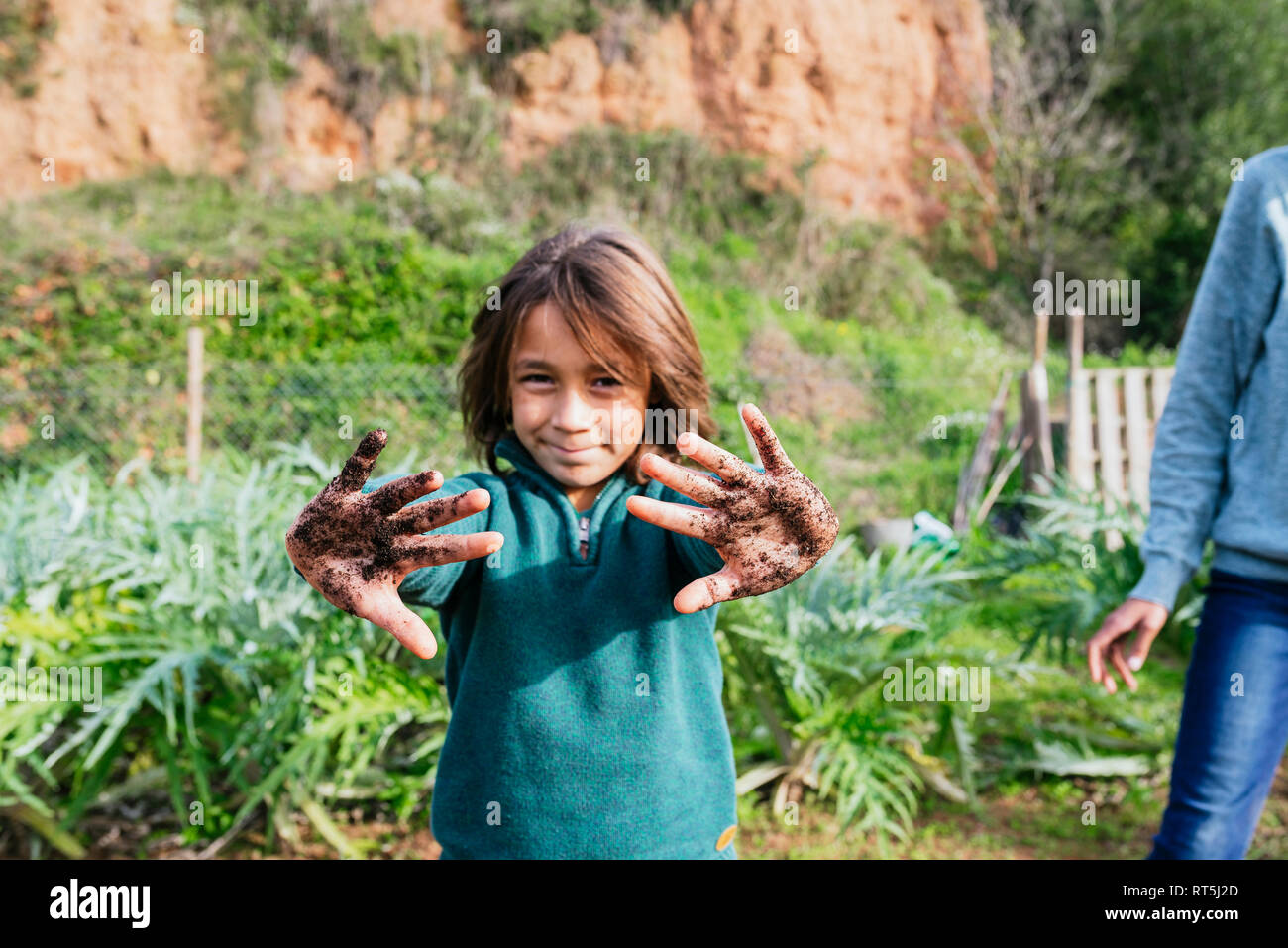 Boy showing his messy hands, full of soil - Stock Image