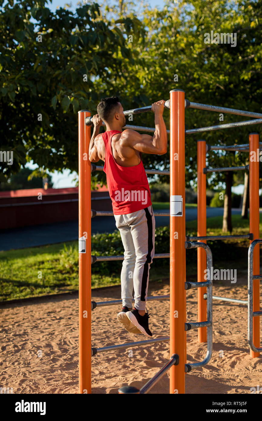 Fit man working out in climbing parcour, doing pull ups - Stock Image