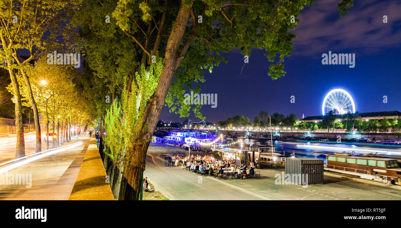 France, Paris, Champs-Elysees, Quai Anatole, people at River Seine bank at night - Stock Image