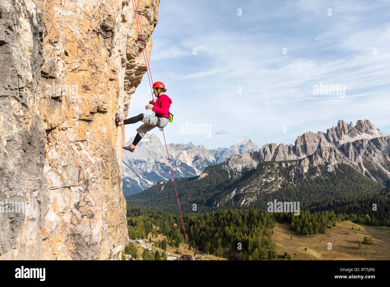 Italy, Cortina d'Ampezzo, woman abseiling in the Dolomites mountains Stock Photo