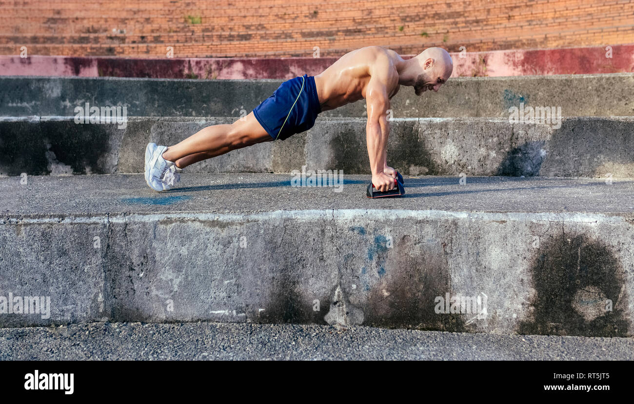 Barechested muscular man doing push-ups outdoors - Stock Image