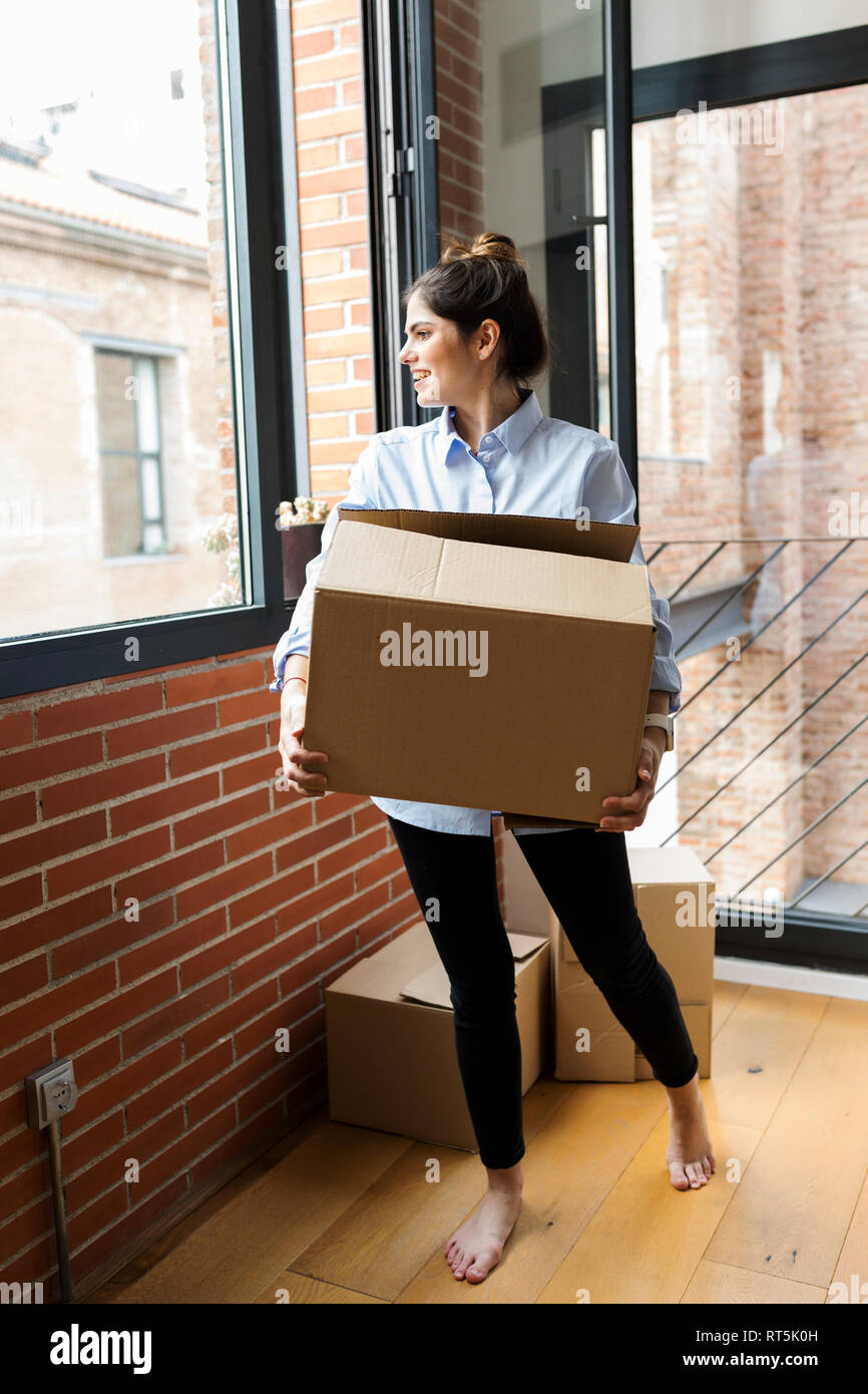 Smiling young woman carrying cardboard box in new apartment looking out of window - Stock Image