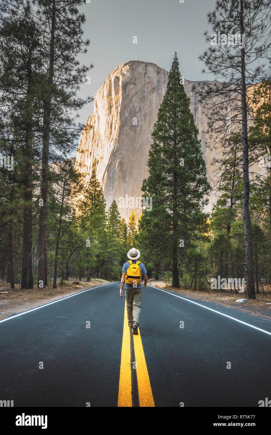 USA, California, Yosemite National Park, man walking on road with El Capitan in background Stock Photo
