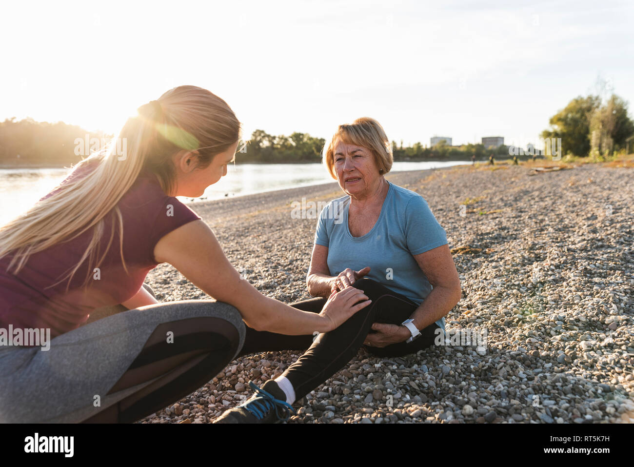 Granddaughter examining aching knee of her grandmother after training at the river - Stock Image