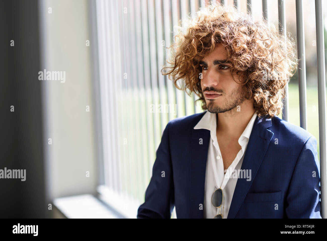 Portrait of young fashionable man with beard and curly hair Stock Photo