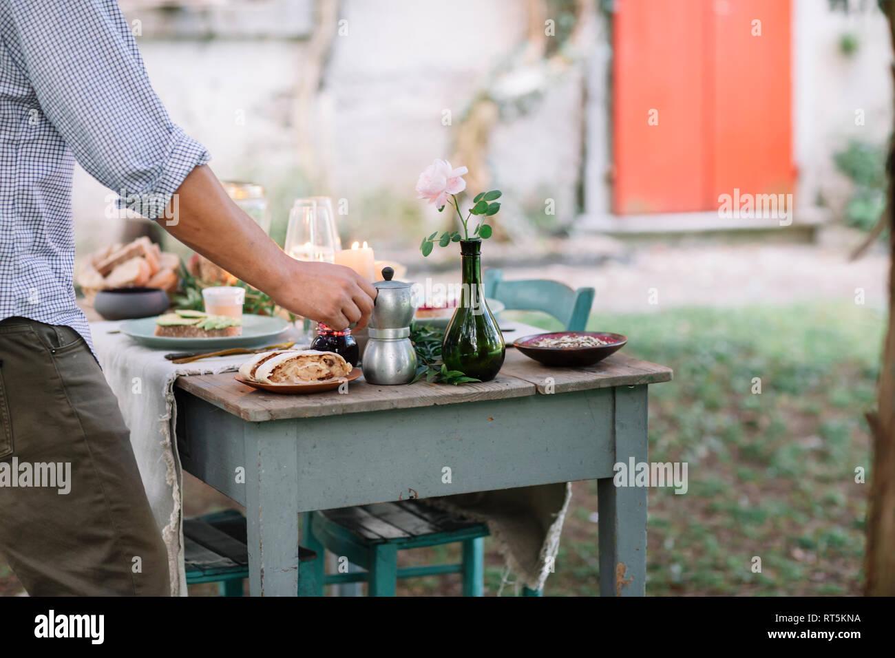 Close-up of man taking moka pot from garden table - Stock Image
