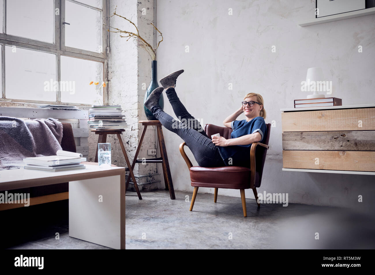 Happy woman sitting with legs in the air on armchair in loft - Stock Image
