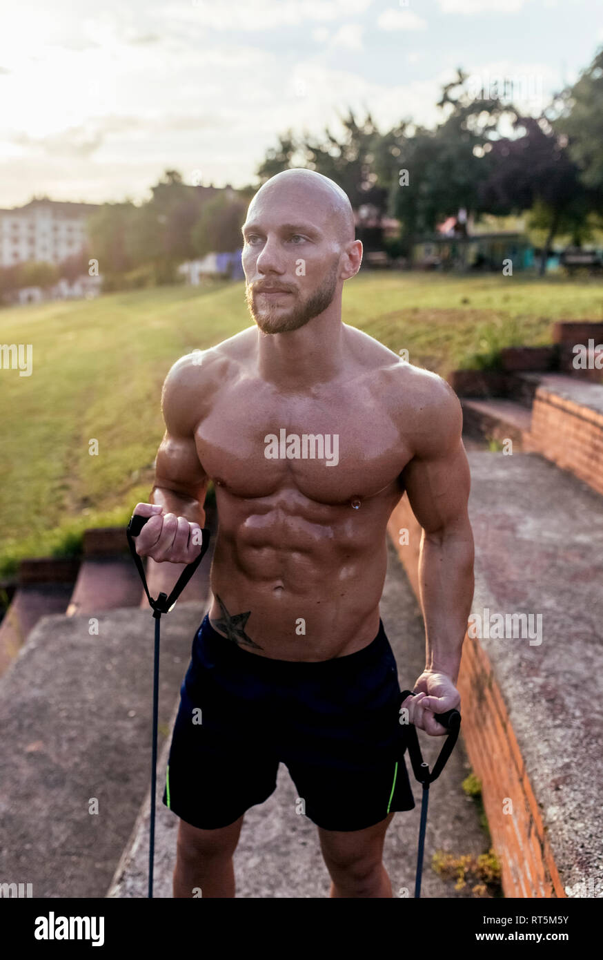 Barechested muscular man exercising with expander outdoors - Stock Image