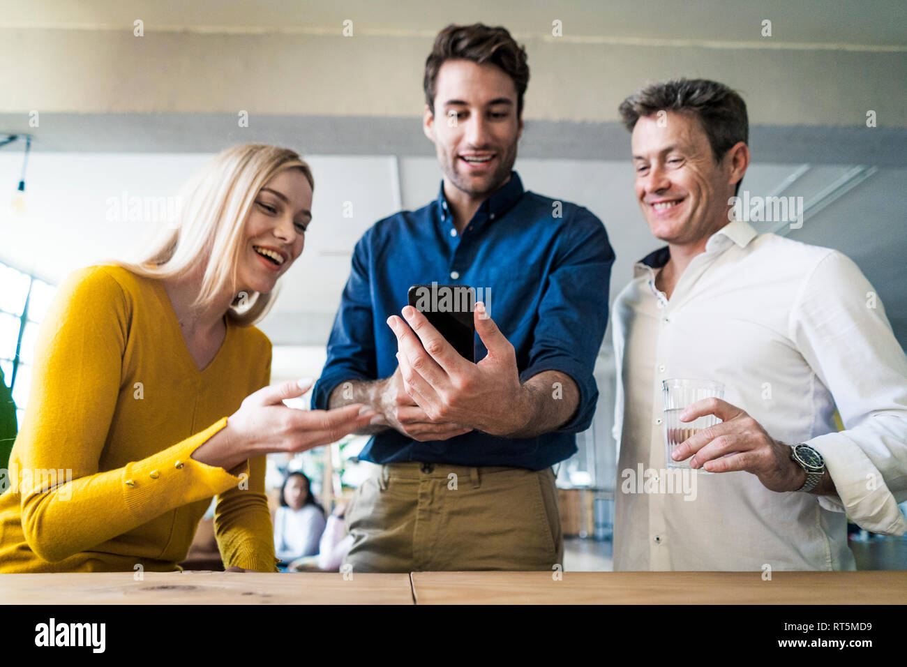 Happy business team looking at cell phone together in loft office - Stock Image