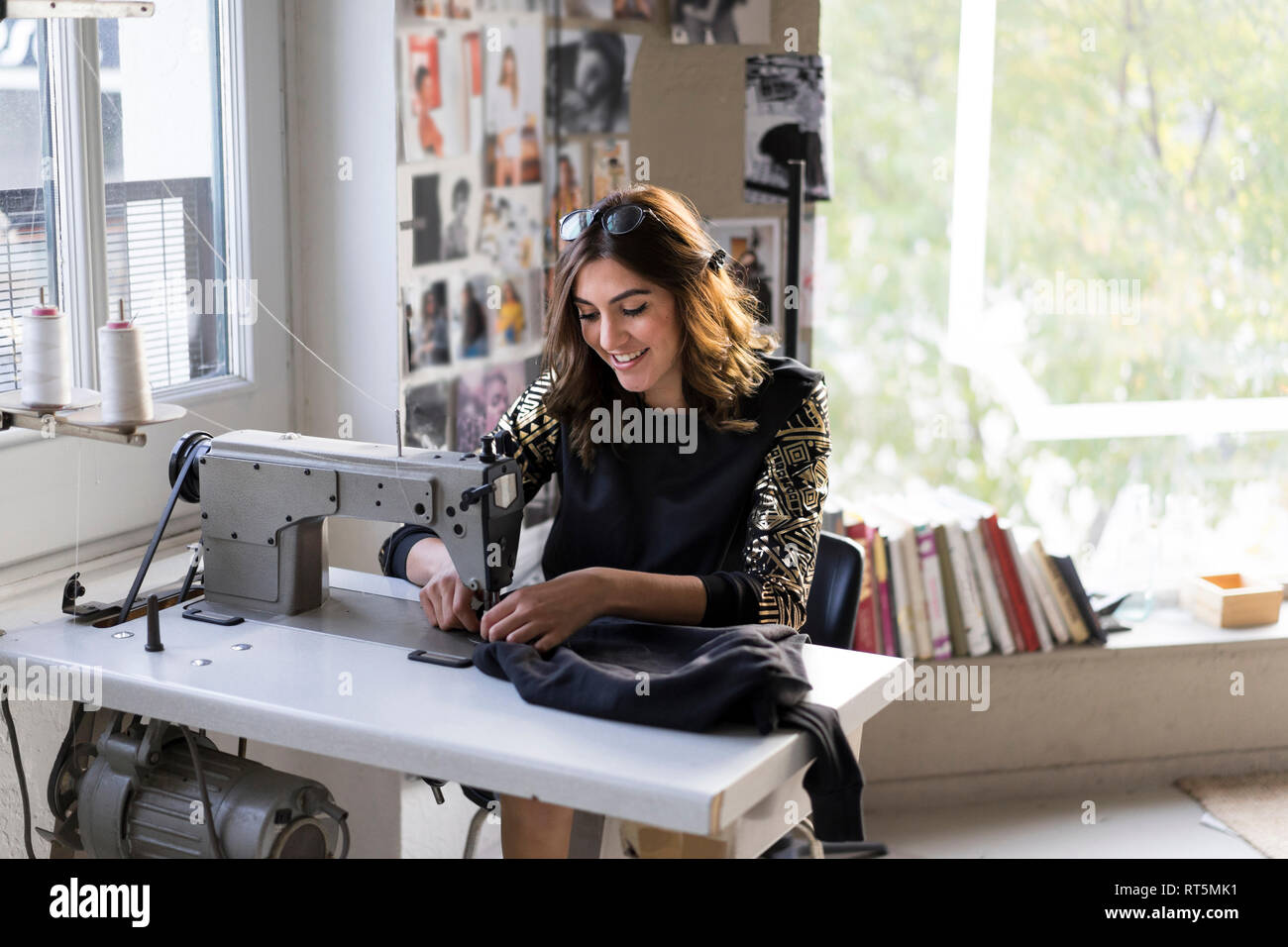Smiling Young Fashion Designer Using Sewing Machine In Her Atelier Stock Photo Alamy