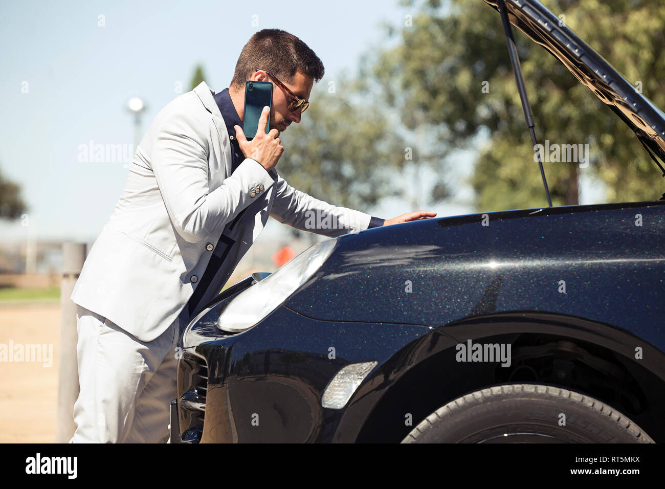 Young businessman having a car breakdown, talking on the phone - Stock Image