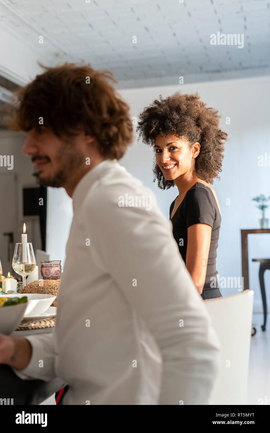 Friends having fun at a dinner party, enjoying eating together - Stock Image
