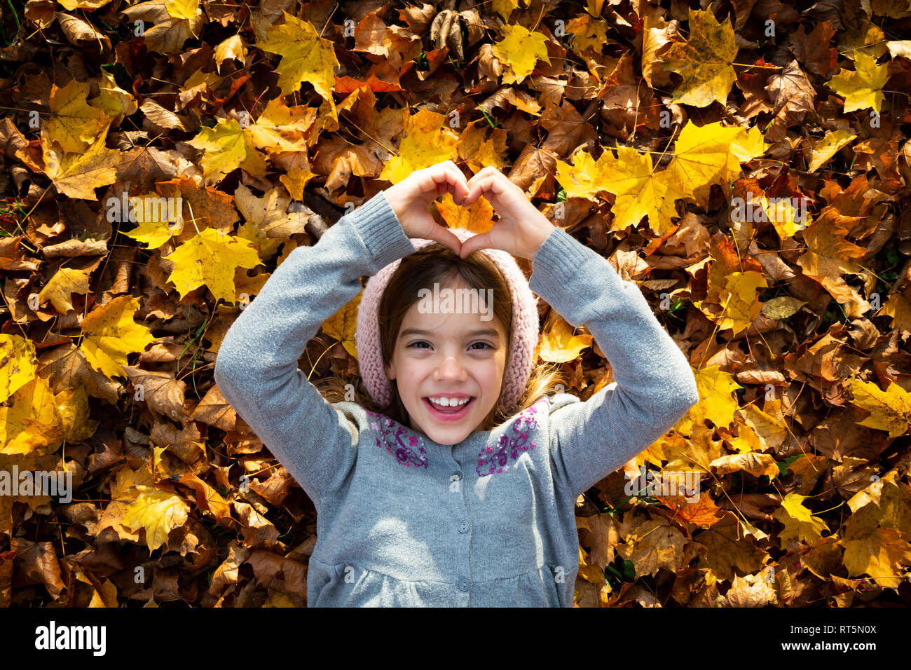 Portrait of happy little girl lying on autumn leaves shaping heart with her hands - Stock Image