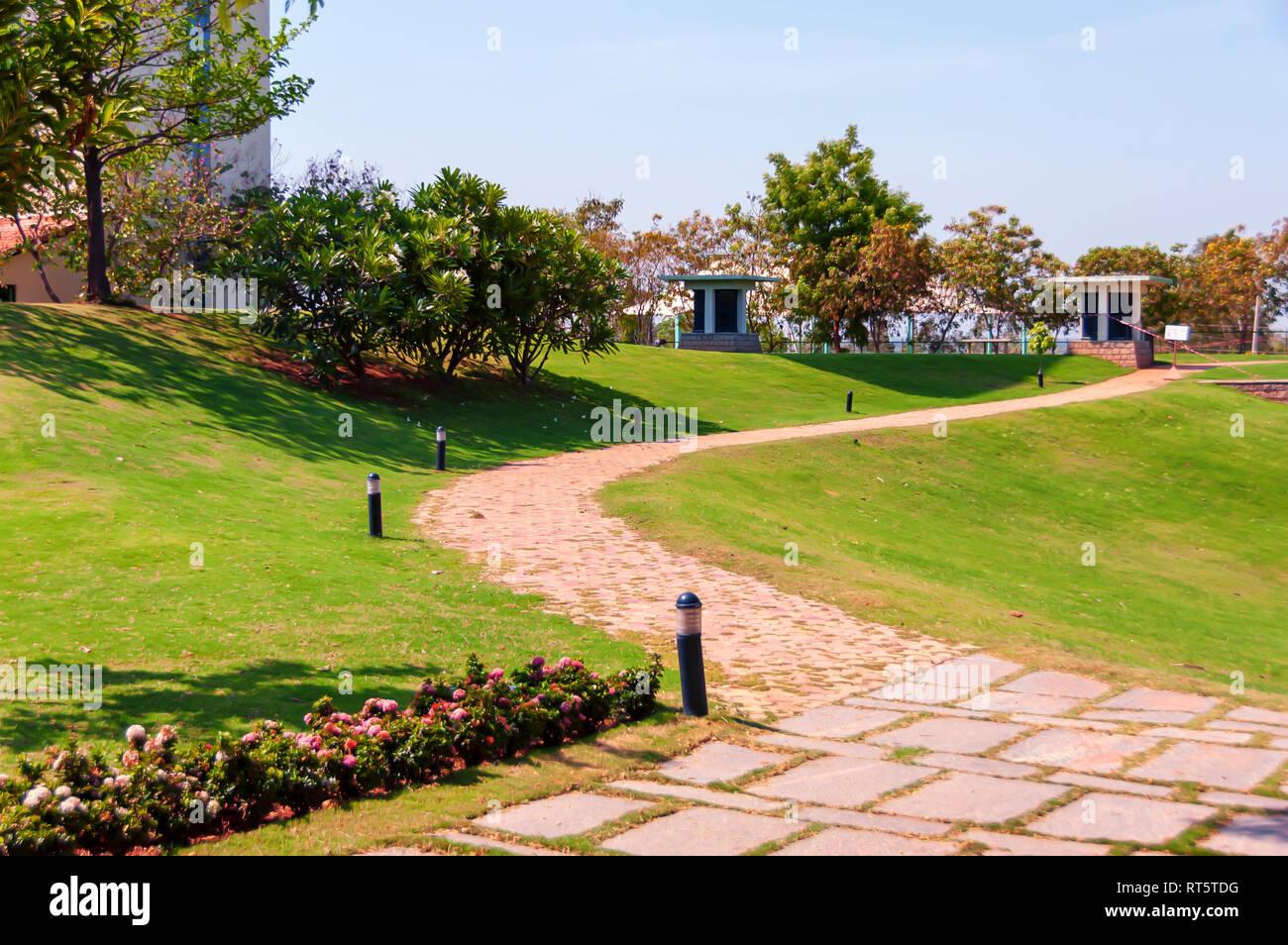 A curved path through a green lawn on a bright sunny day at Golkonda Resorts and Spa at Hyderabad, Telangana, India. - Stock Image