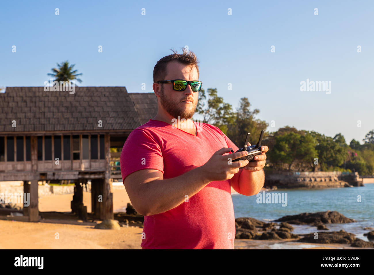 A man controls a drone at sunset - Stock Image