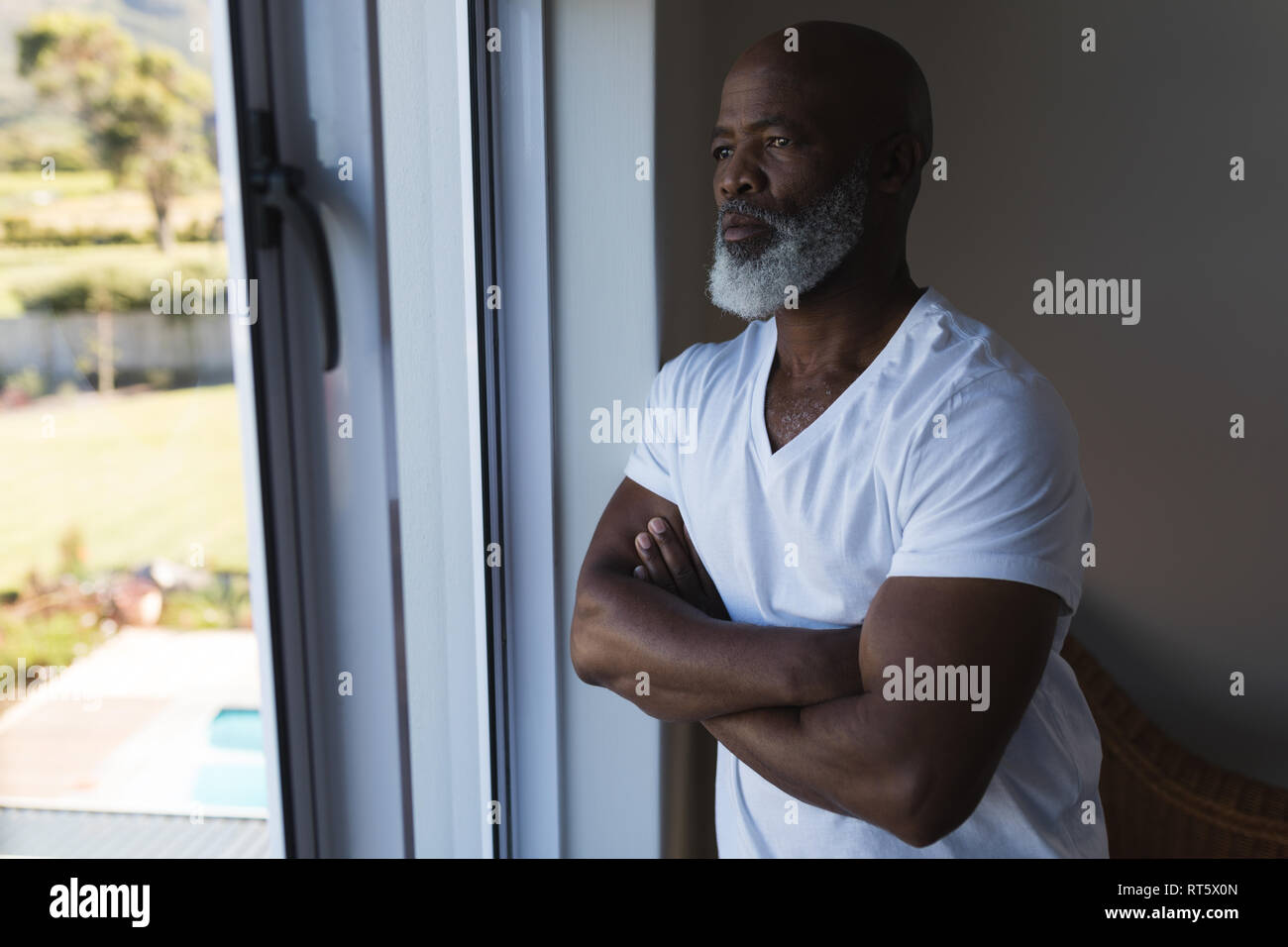 Senior man looking through window with arms crossed at home - Stock Image