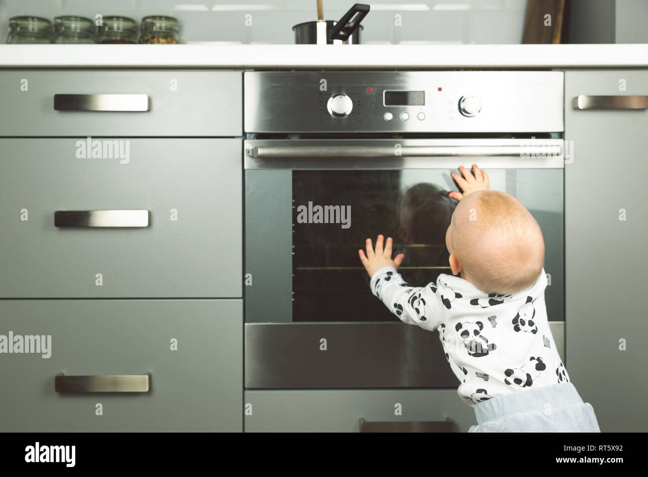 Little Child Playing With Electric Stove In The Kitchen. Baby Safety In  Kitchen