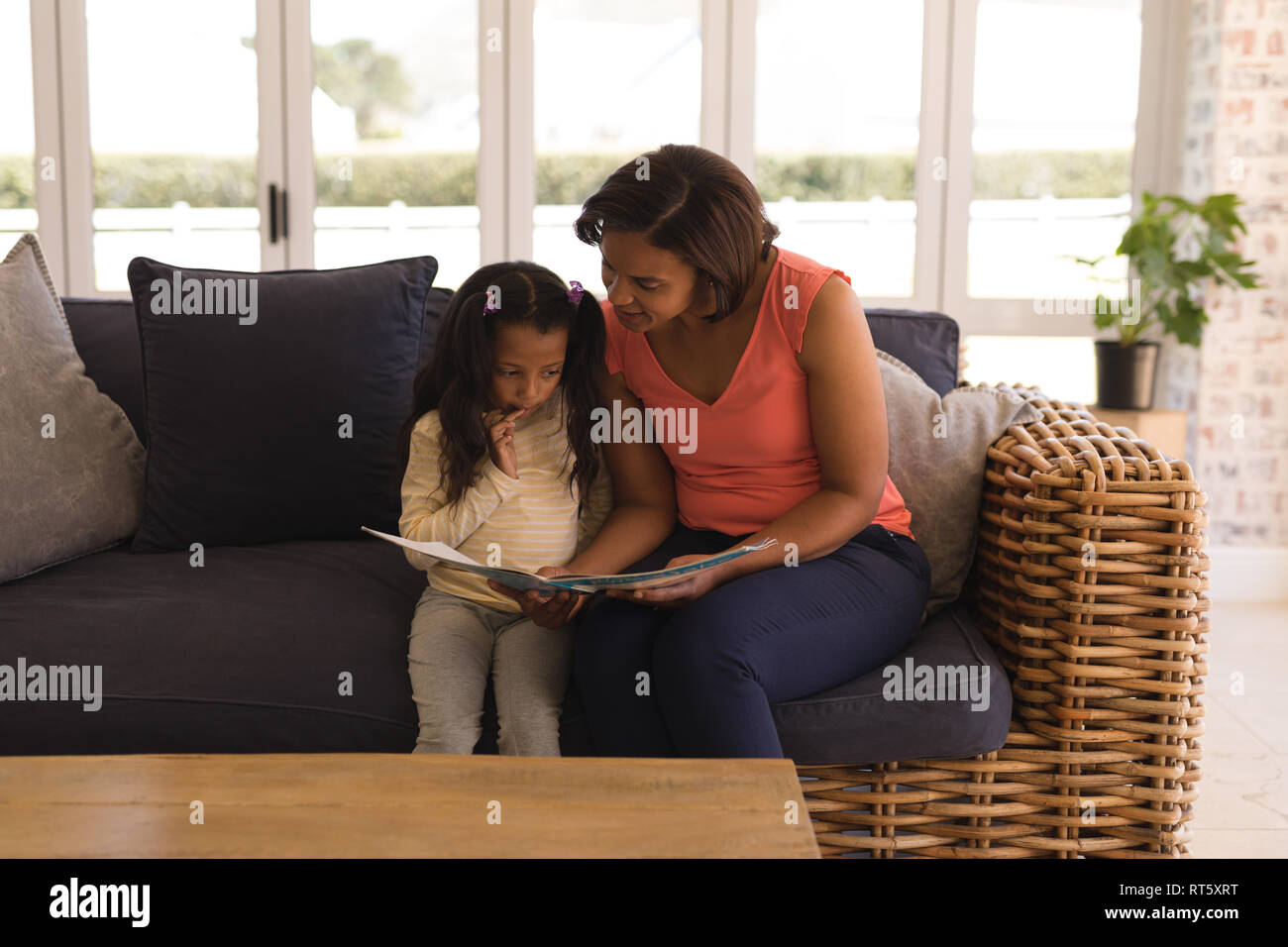 Grandmother and granddaughter reading a story book in living room - Stock Image