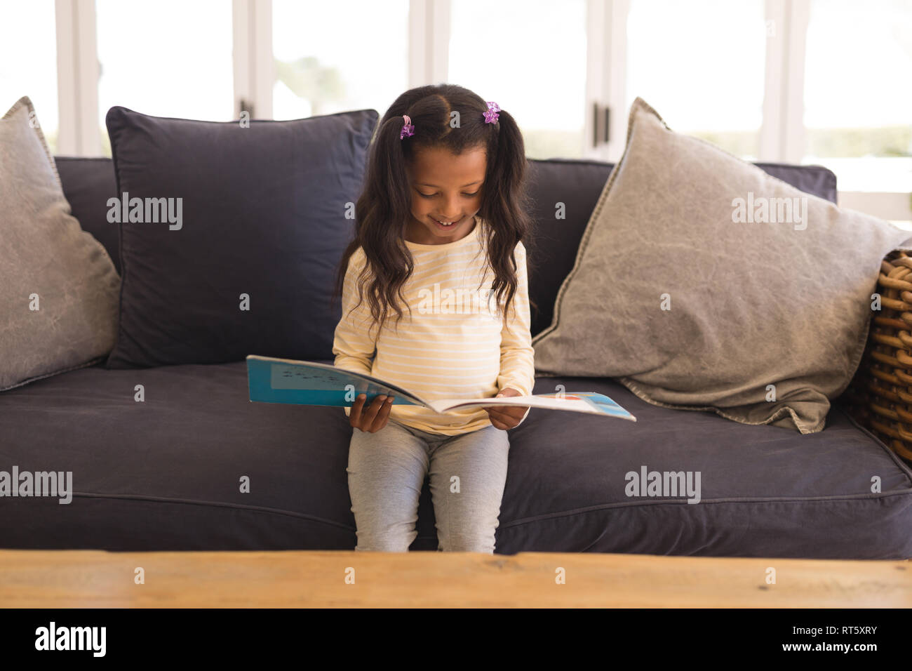 Girl reading a story book in living room - Stock Image