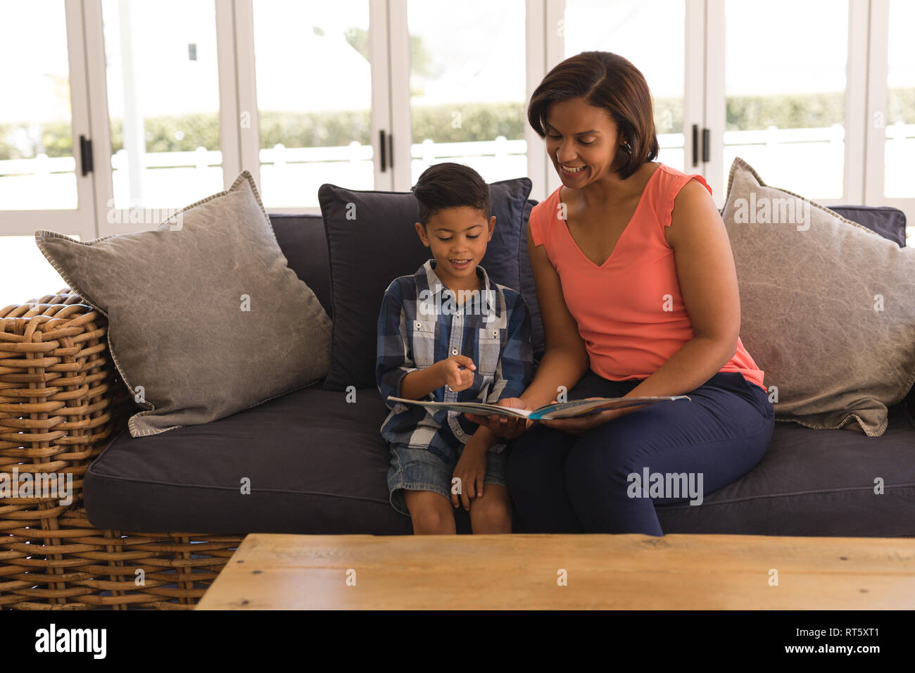 Grandmother and grandson reading a story book in living room - Stock Image