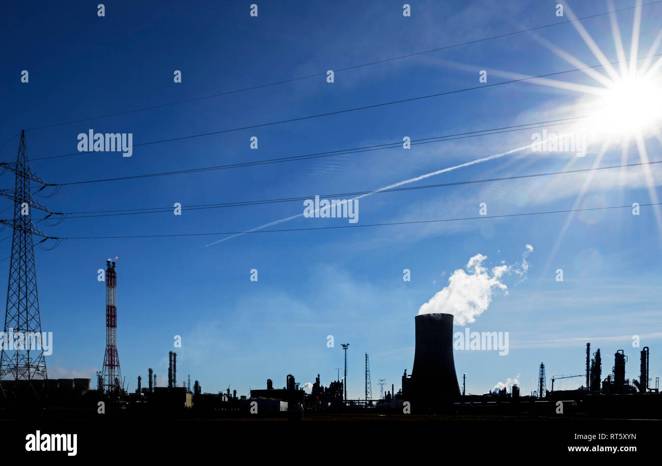Silhouette of industrial estate showing cooling tower of the BASF chemical production site in the port of Antwerp, Belgium - Stock Image