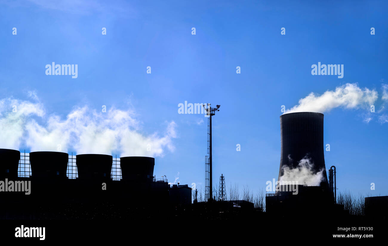 Industrial estate showing cooling tower and chimneys silhouetted against blue sky at the BASF chemical production site in the port of Antwerp, Belgium - Stock Image