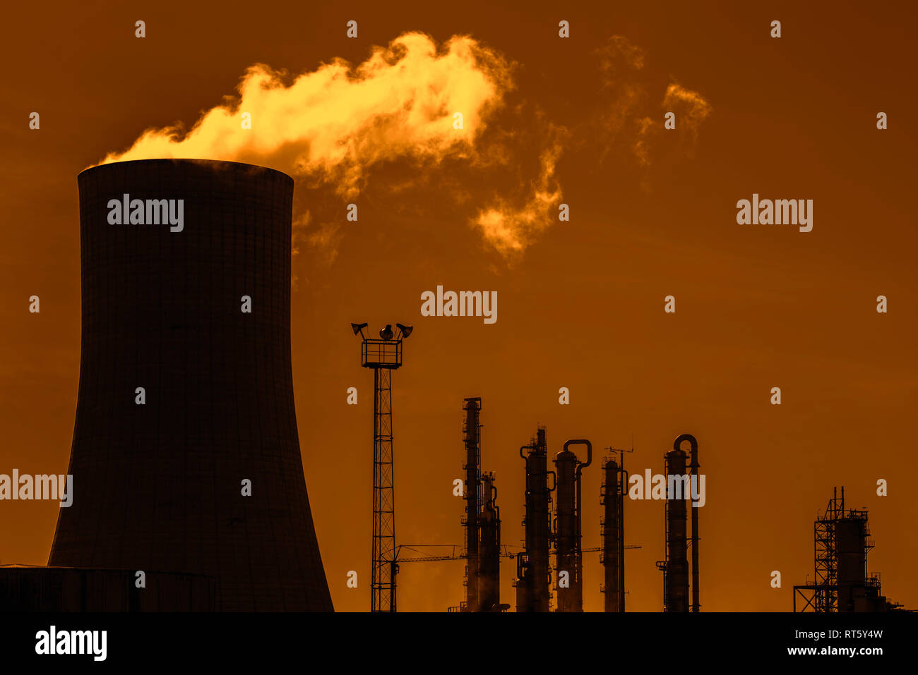 Industrial estate showing cooling tower silhouetted against sunset at the BASF chemical production site in the port of Antwerp, Belgium - Stock Image