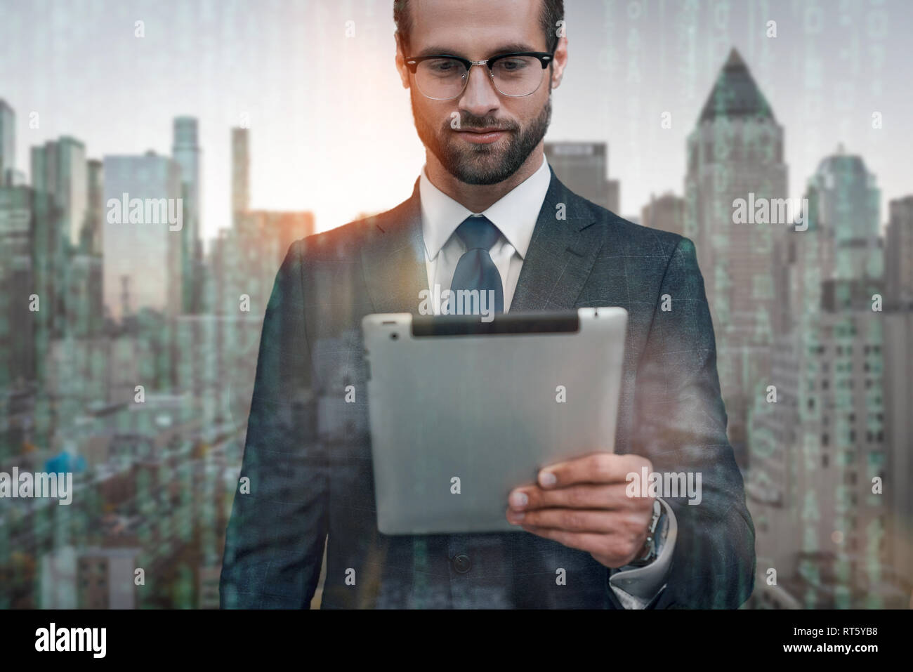 Always connected. Positive businessman working on digital tablet while standing outdoors with modern office buildings on the background. Digital. Technologies. Business look - Stock Image