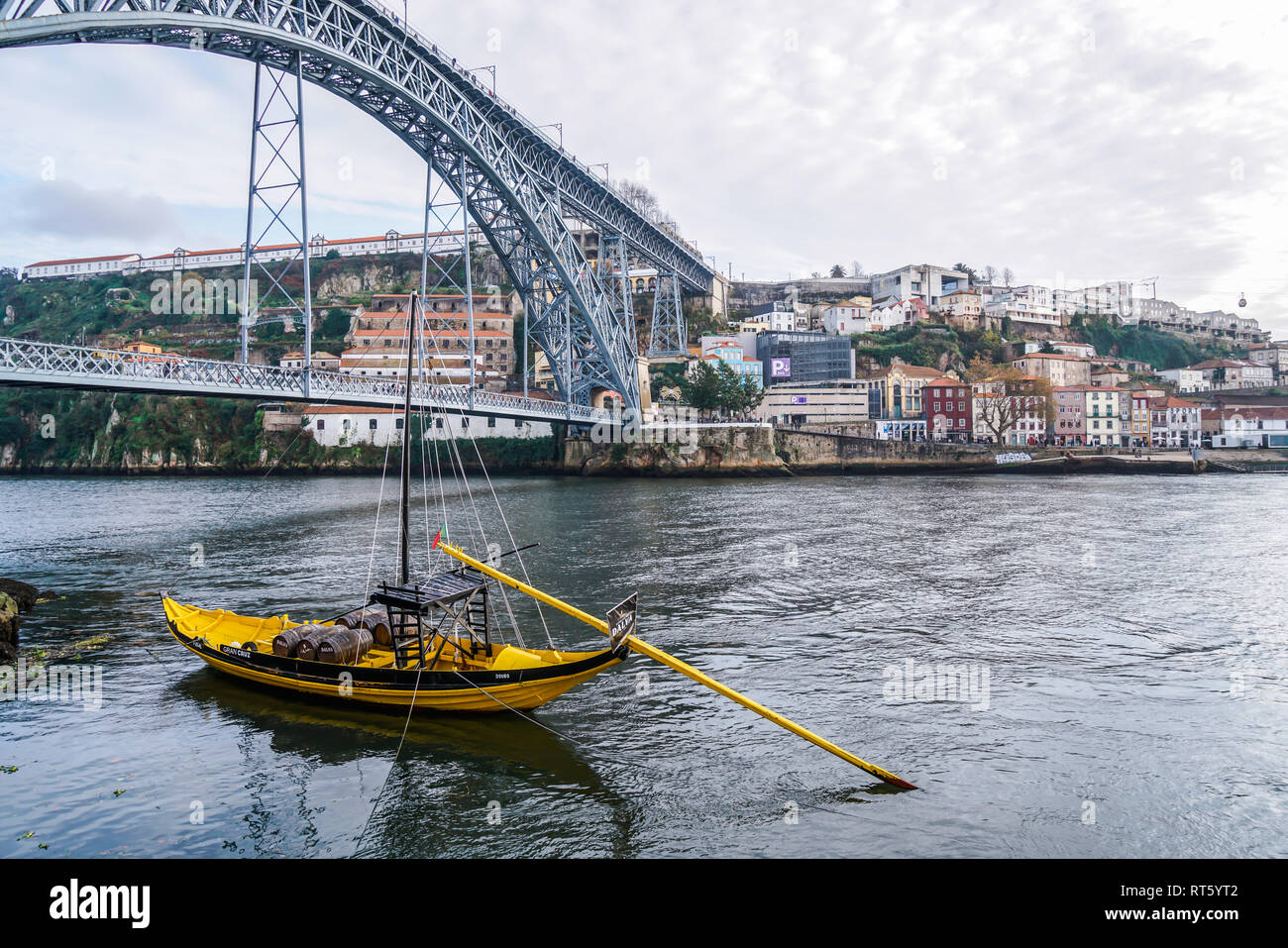 Porto, Portugal - December 2018: Yellow Rabelo Boat transporting port wine, in Douro River with Luis I Bridge behind. Stock Photo