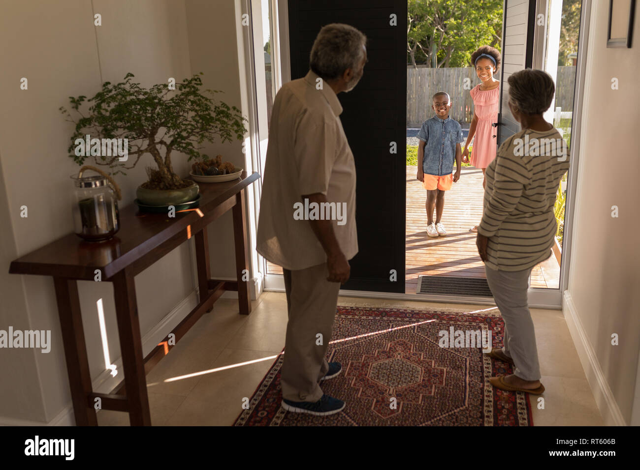 Grandparents standing near door and inviting their grandchildren in home - Stock Image