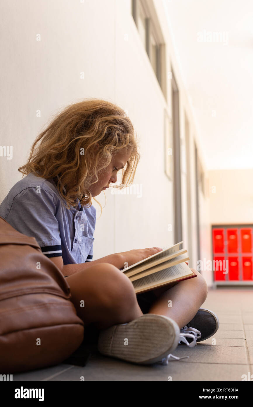Schoolgirl with school bag sitting on floor and reading a