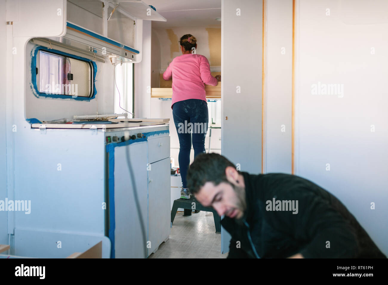 Young couple painting and restoring caravan - Stock Image