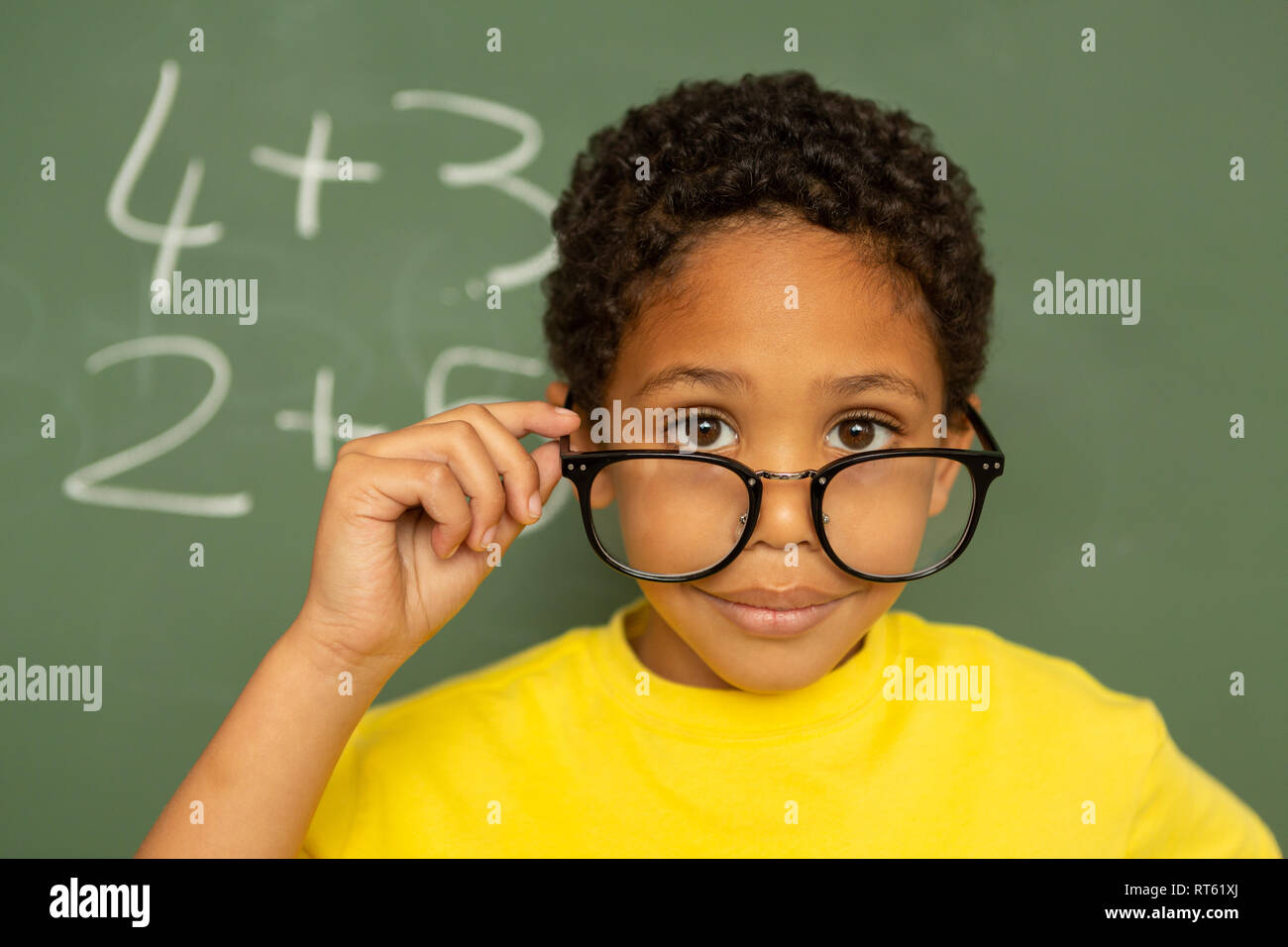 Happy schoolboy looking over spectacle against greenboard in a classroom - Stock Image