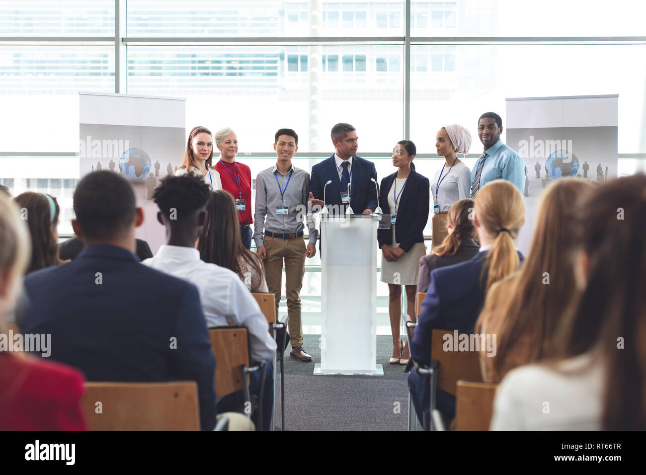 Businessman standing at podium with colleagues and speaks in a business seminar - Stock Image