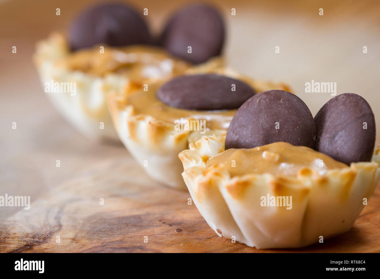 baked phyllo dough cups filled with peanut butter topped with dark chocolate wafers Stock Photo
