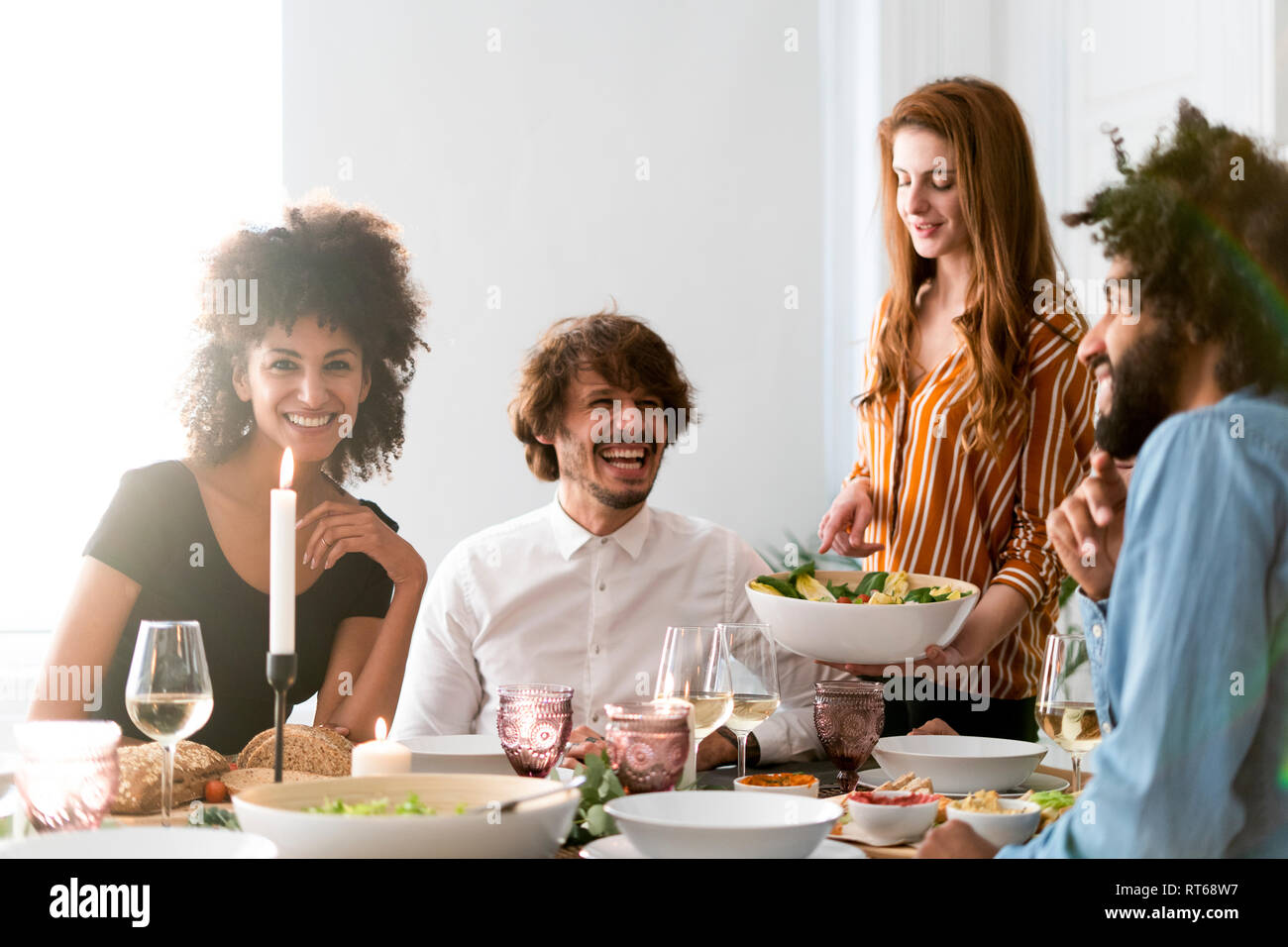 Friends having fun at a dinner party, enjoying eating together Stock Photo