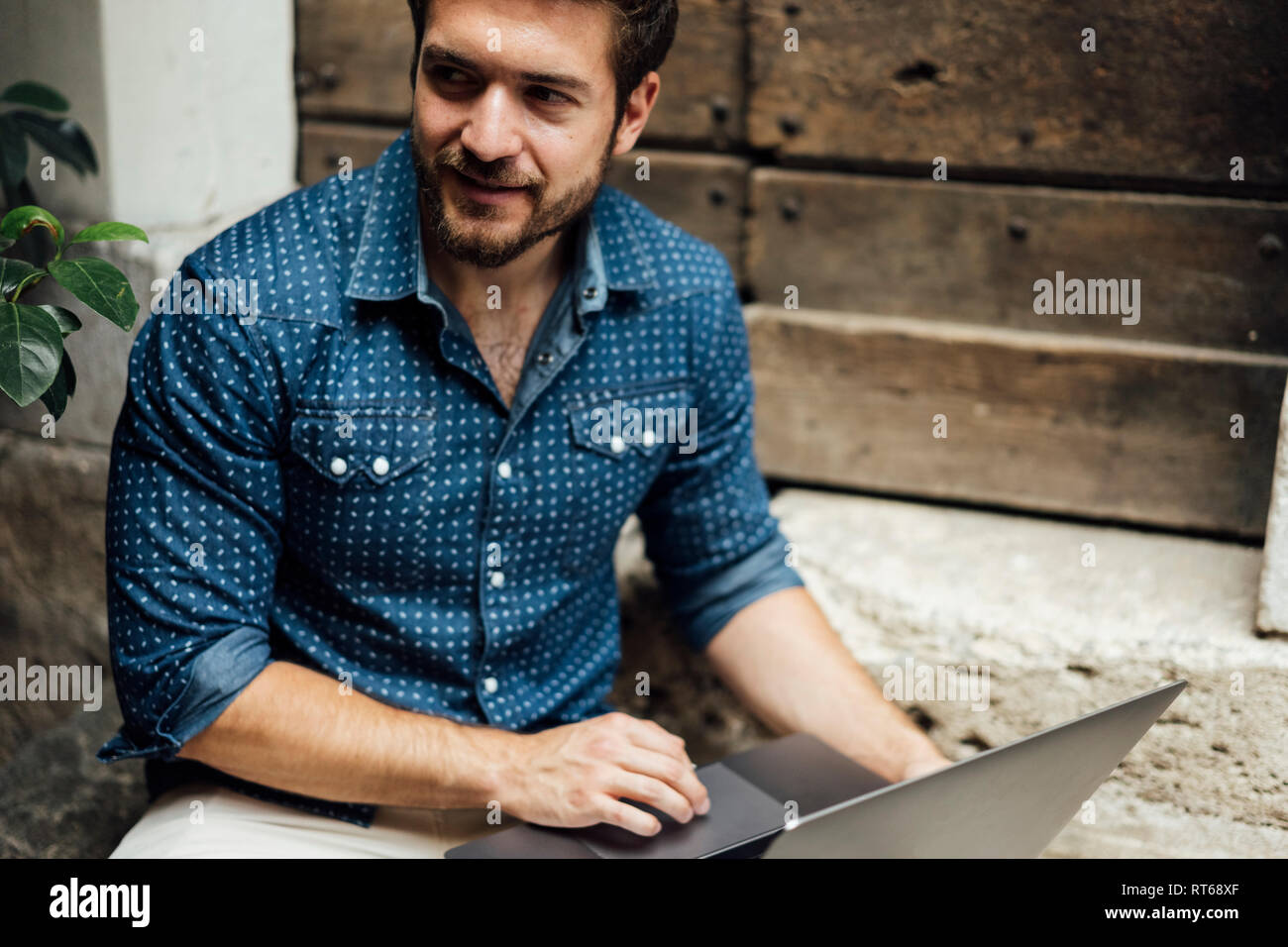 Businessman with laptop sitting on steps in a courtyard watching something - Stock Image