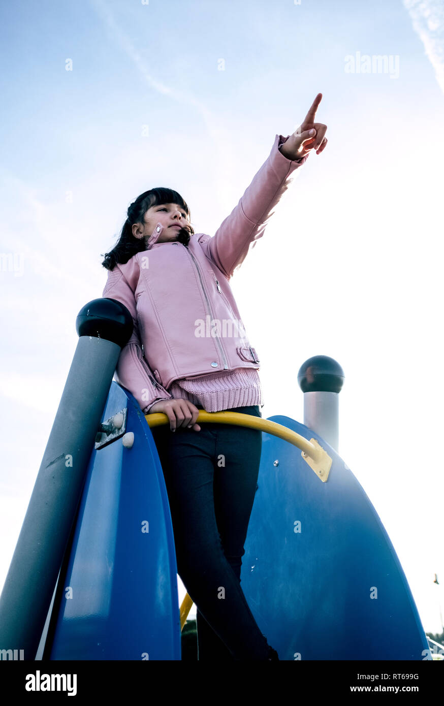 Girl wearing pink leather jacket on playground pointing on something at distance - Stock Image