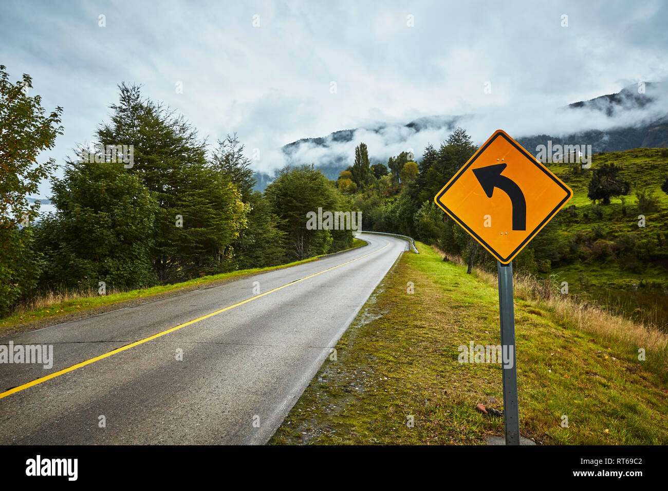 Chile, Puerto Aysen, country road in autumn with curve road sign - Stock Image