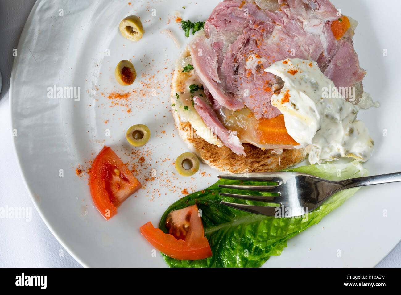 Entree dish of Ham hock terrine on buttered toast with a natural yogurt dip - Stock Image
