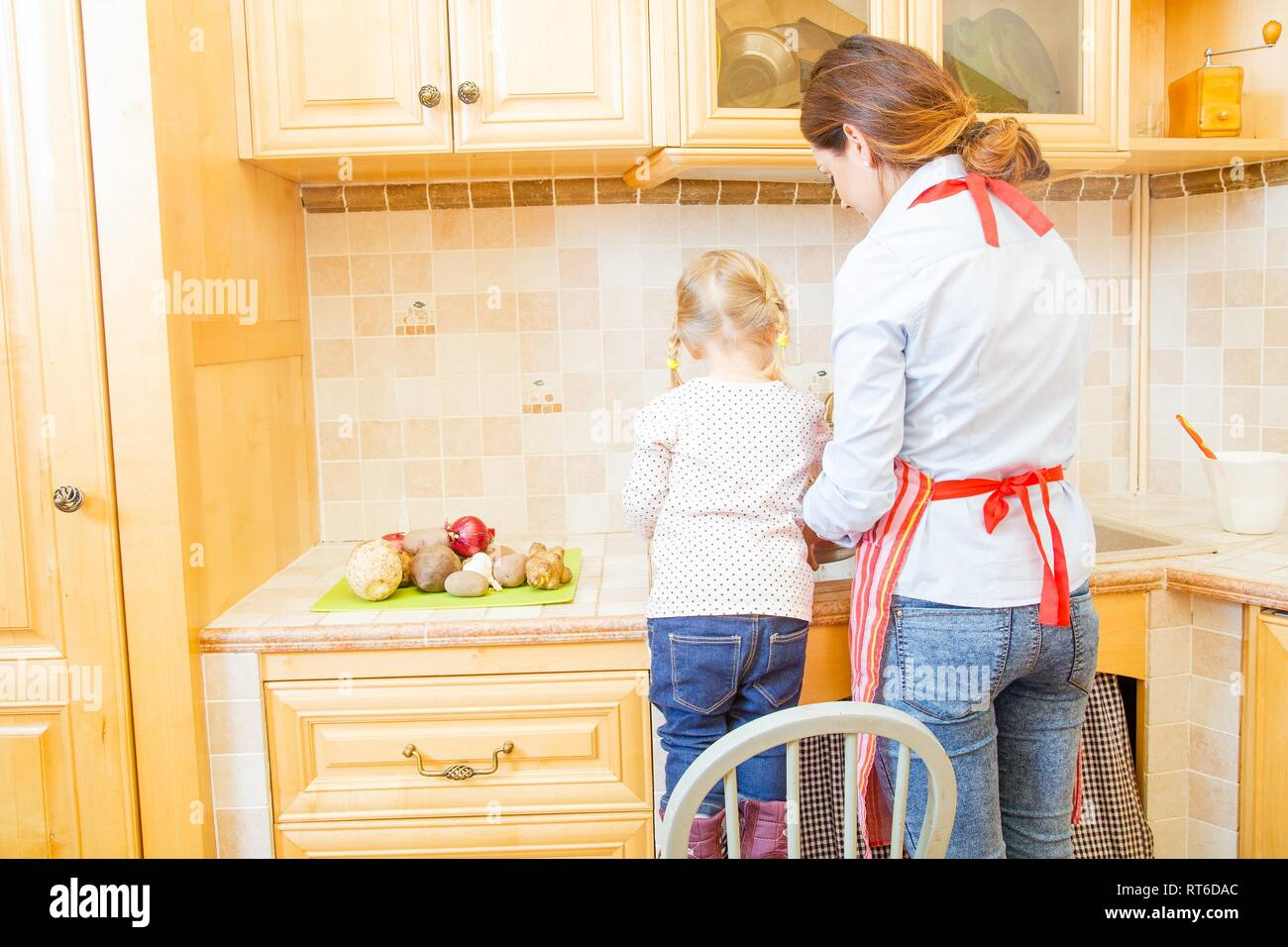 Helping hand given in the kitchen by little daughter. - Stock Image