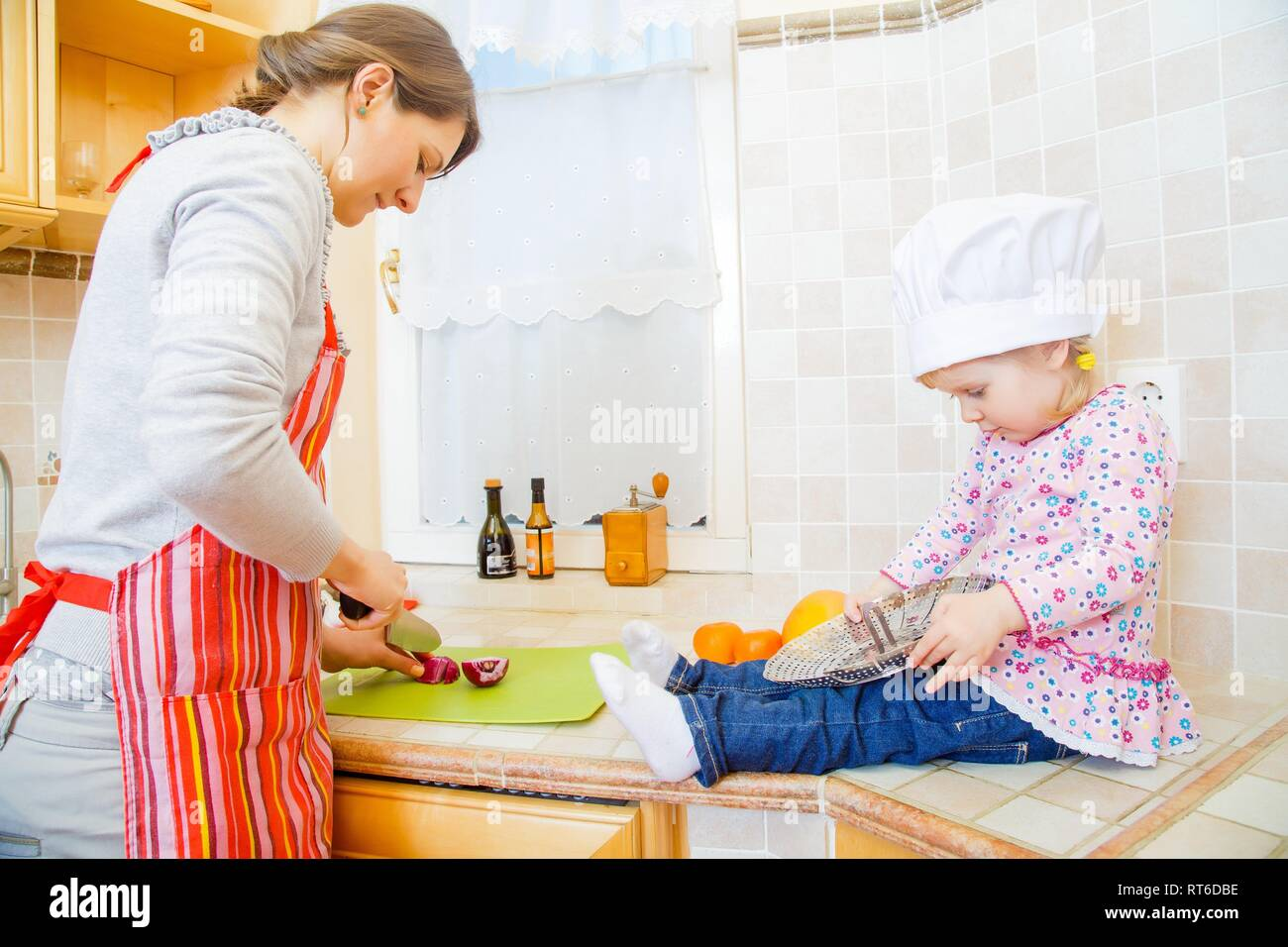 Little girl and mother cooking together in the kitchen. - Stock Image