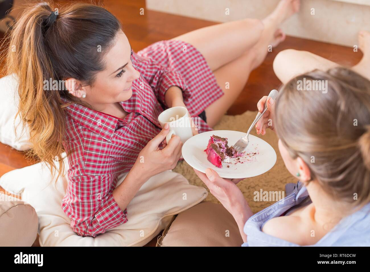 Women chitchatting with best friend at home near a tea. - Stock Image