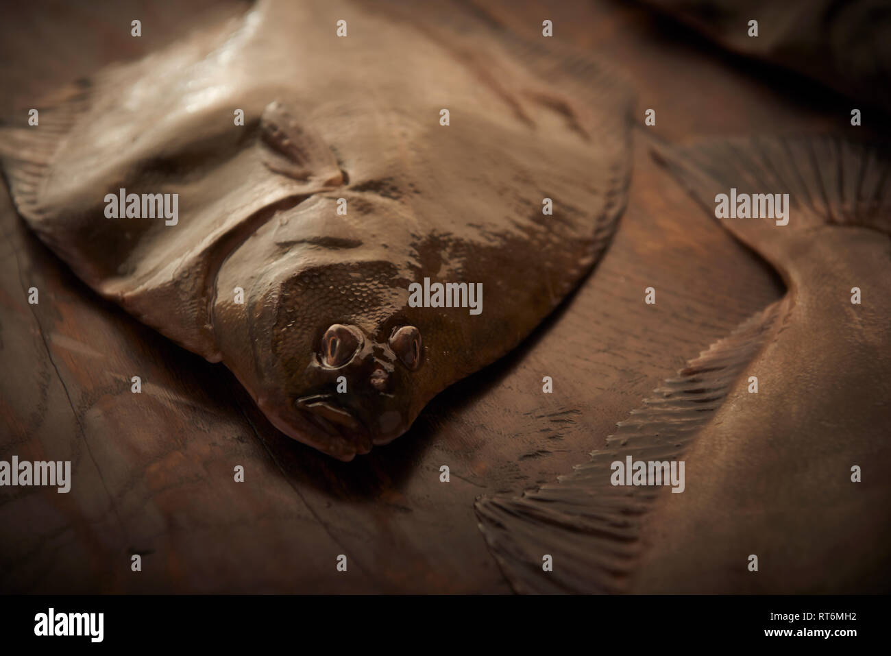 Flatfish lying on a timber table ready to be prepared for cooking. - Stock Image