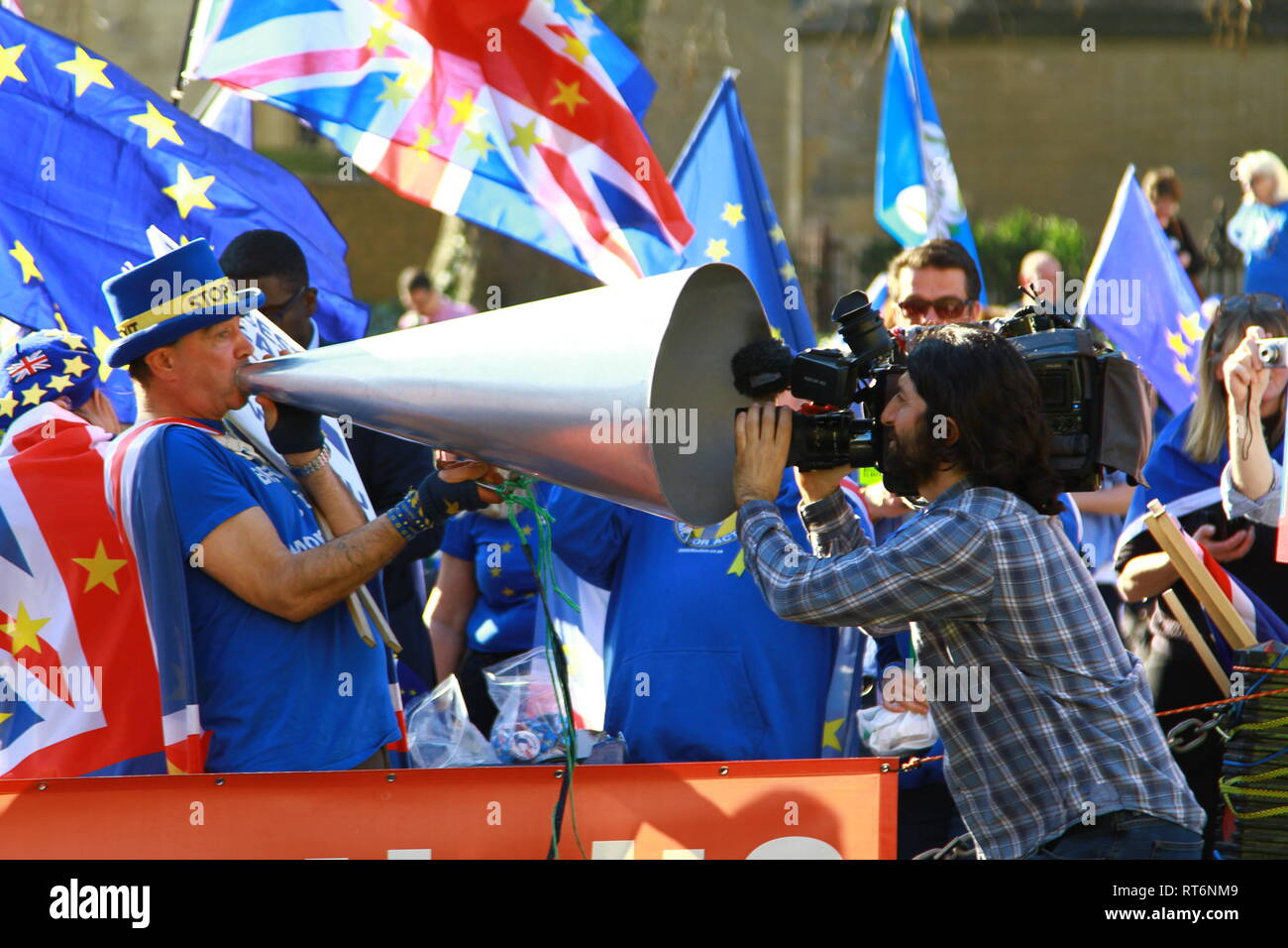STOP BREXIT CAMPAIGNER STEVE BRAY SHOUTS STOP BREXIT THROUGH A MASSIVE LOUD SPEAKER AND A MOVIE CAMERA RECORDS THE EVENT AT THE SHARP END. PRO EUROPE. ANTI BREXIT. STOP BREXIT PROTEST OUTSIDE THE PALACE OF WESTMINSTER WITH STEVE BRAY TAKING A DEDICATED PASSIONATE LEADING ROLE. AND GOOD FOR HIM. Stock Photo