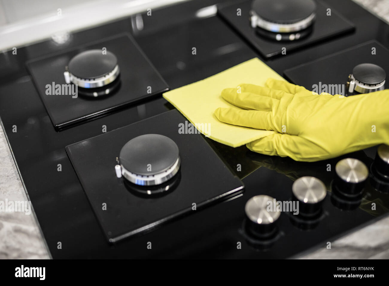 Woman hand with a yellow microfiber cloth rubs a glass ceramic stove in the kitchen. - Stock Image