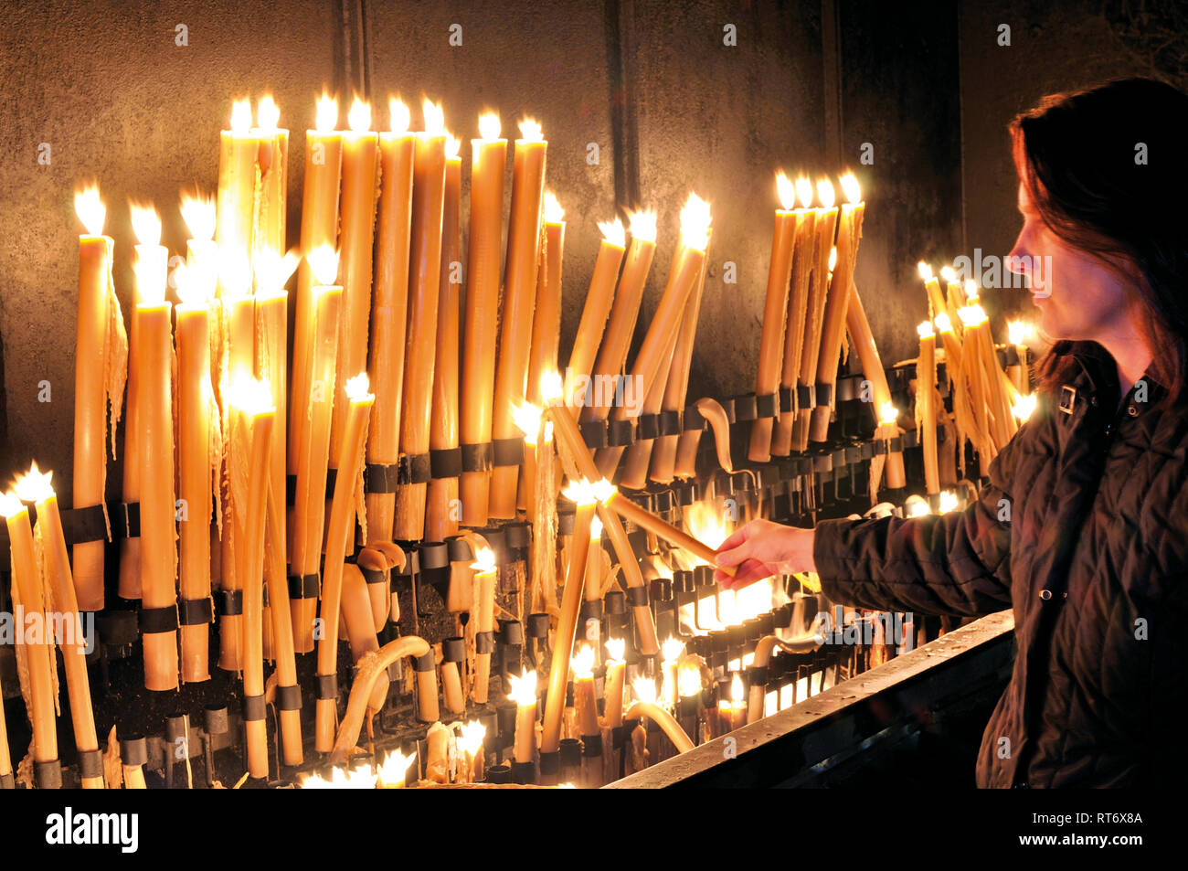 Woman lightening a candle at devotion altar - Stock Image