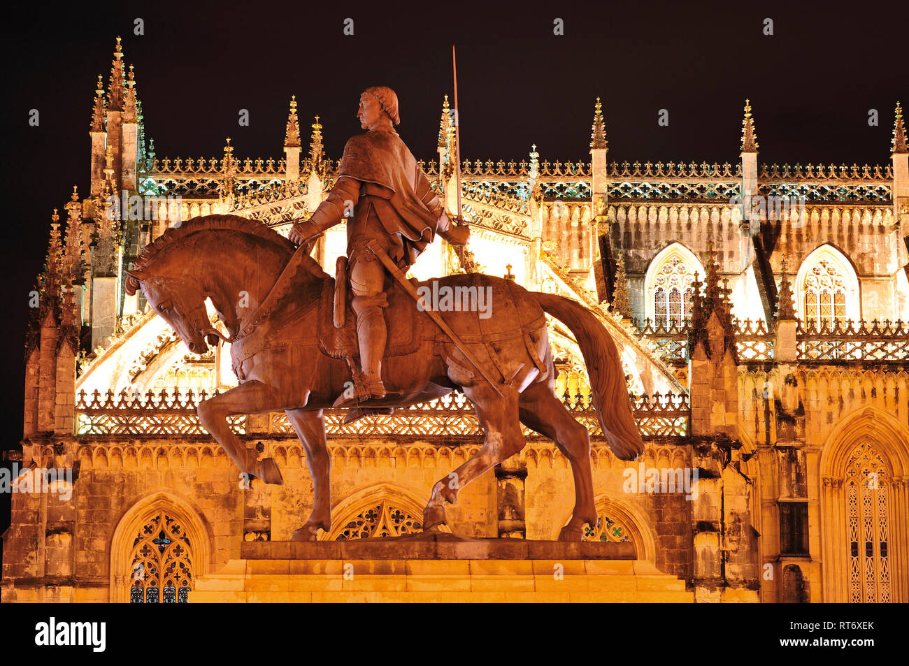 Nocturnal and lateral view of gothic monastery and pedestrian statue of medieval knight - Stock Image