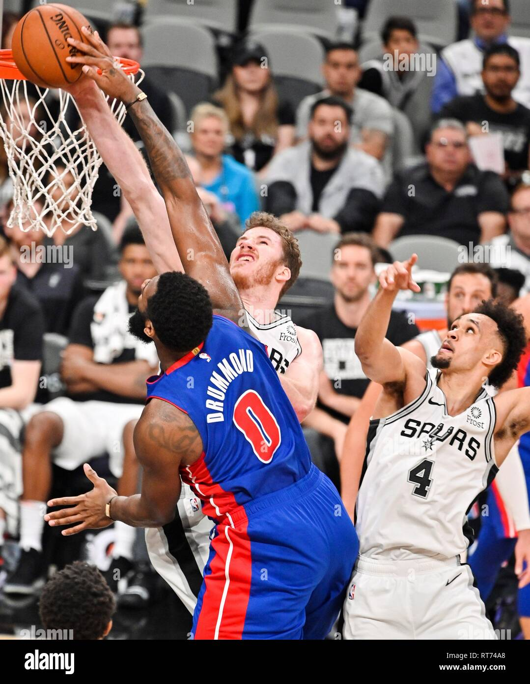 San Antonio, Texas, USA. 27th Feb, 2019. Jakob Poeltl (back) of the San Antonio Spurs blocks a slam dunk attempt by Andre Drummond (L) of the Detroit Pistons as Spurs guard Derrick White looks on during an NBA basketball game against the Detroit Pistons, in San Antonio, Texas, USA, 27 February, 2019. Credit: Darren Abate/EFE/Alamy Live News Stock Photo